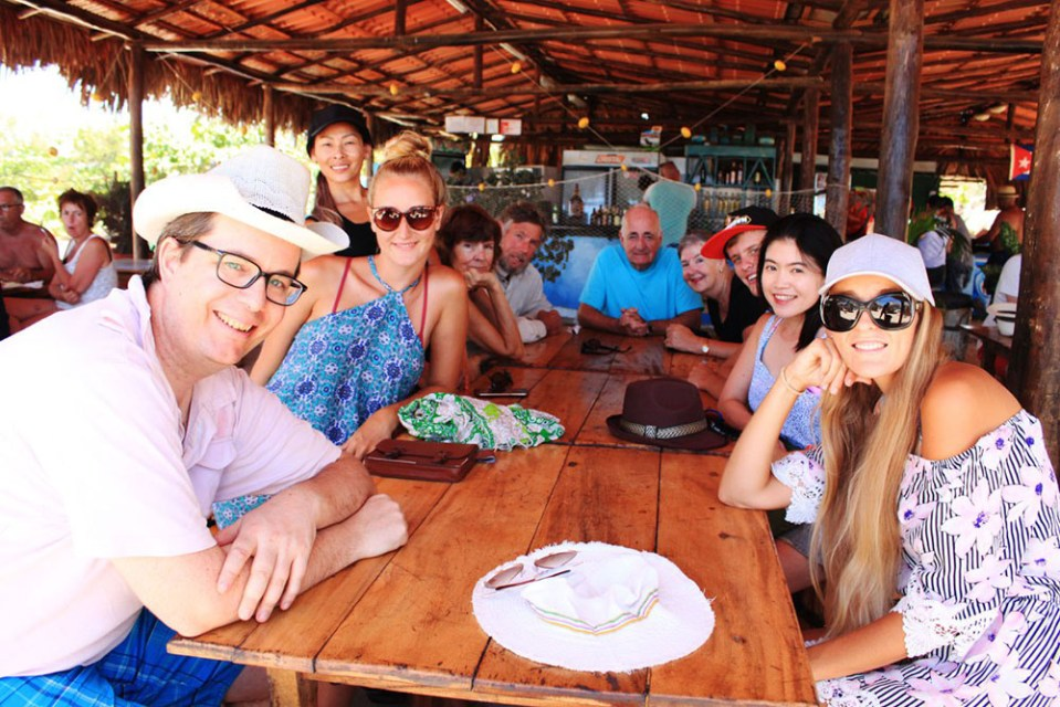 mix group european asian traveler in Playa Ancon Cuba beach sitting restaurant table