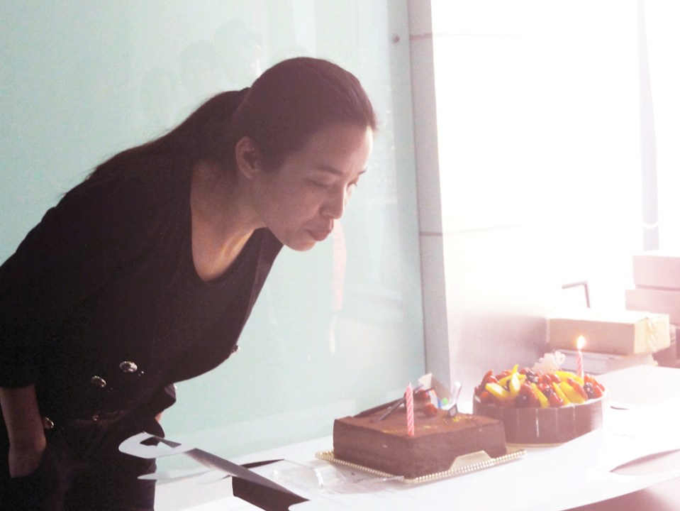asian woman lady boss dressed in black blowing birthday candle chocolate cake agirlnamedclara