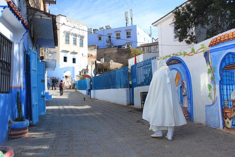 man white cap walking on street chefchaouen pearl of morocco_agirlnamedclara