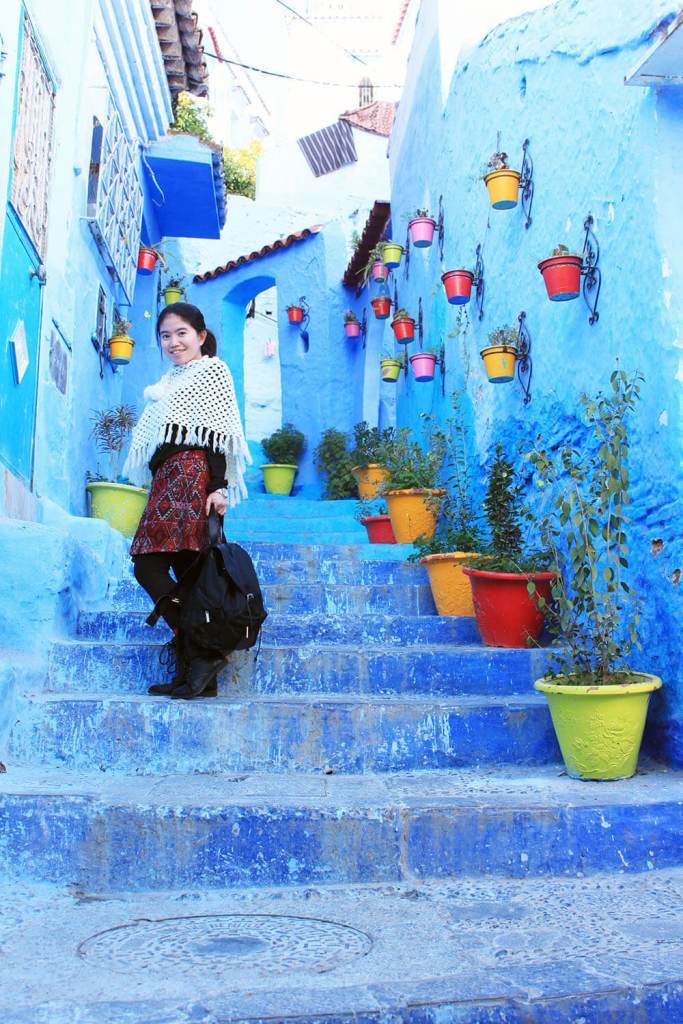 girl white poncho red skirt boots stairs chefchaouen blue city morocco_agirlnamedclara