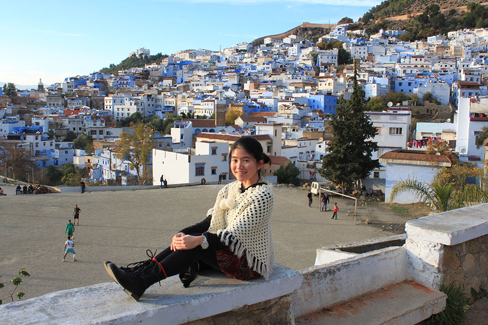 agirlnamedclara_asian girl white poncho red skirt black boots sit chefchaouen blue city morocco blue white buildings background sunset