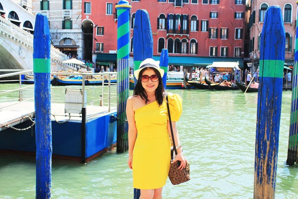 agirlnamedclara_asian girl tourist traveller yellow dress white hat standing at venice canal river