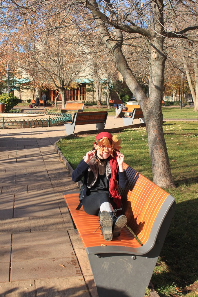 playful girl asian traveler fall autumn leafs ifrane atlas mountains morocco agirlnamedclara sitting on a bench