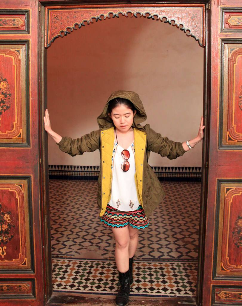 asian girl traveler opens door at Bahia Palace Morocco black boots green jacket agirlnamedclara