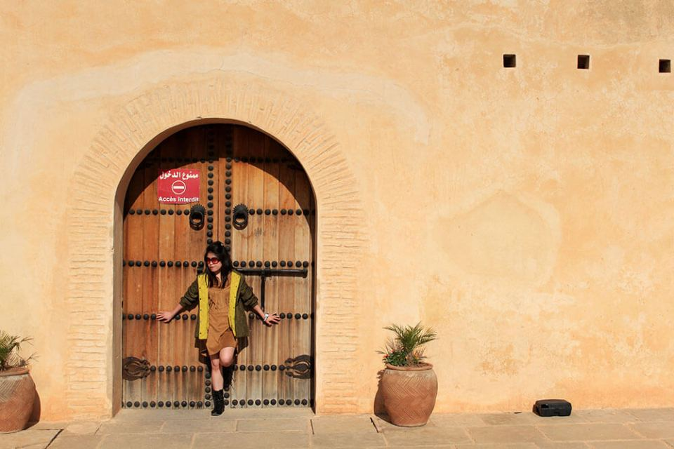 girl short hair standing against a door brown wall morocco travel agirlnamedclara