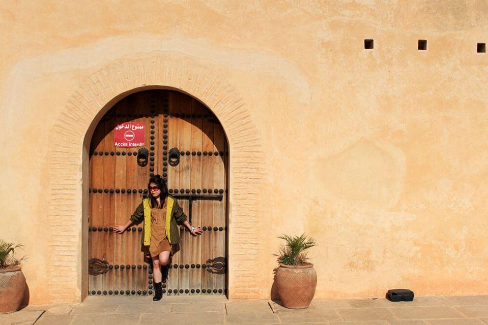 girl short hair standing against a door brown wall morocco travel agirlnamedclara