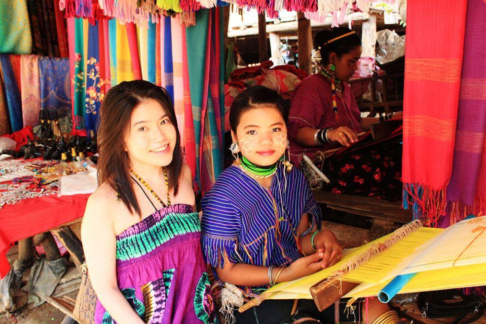 asian girl traveler tourist smiling sitting beside long neck little girl in long neck tribe village chiang mai agirlnamedclara
