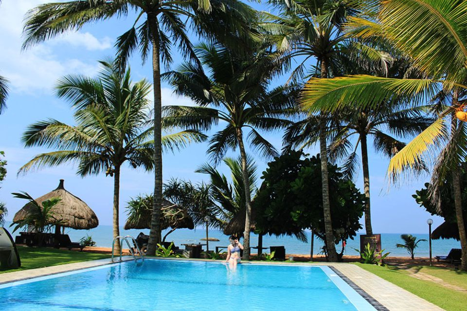 girl in blue bikini sitting at the poolside morning coconut tree blue sky background sea rock villa bentota sri lanka agirlnamedclara