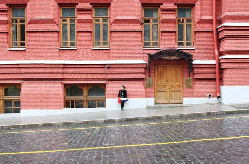 a stranger in moscow asian girl dress alone standing red building background assymetrical road stone agirlnamedclara