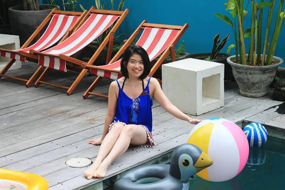 asian girl short hair smilling sits beside swimming pool with toys socialista lifestyle hostel seminyak bali agirlnamedclara