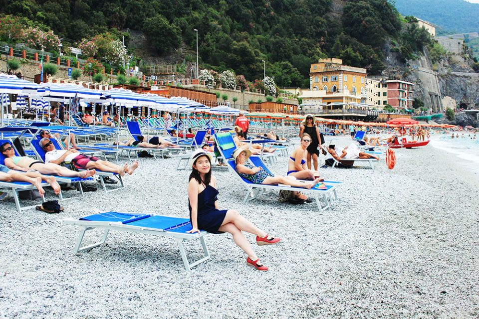 asian girl smiling denim jeans dres sitting on the beach chair cinque terre monterosso italy agirlnamedclara