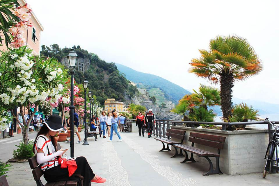 female tourist sitting on public chair in Monterosso Cinque Terre Italy walkway agirlnamedclara