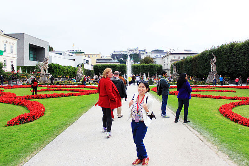 asian girl white blazer smiling stand in the middle mirabell gardens salzburg austria_agirlnamedclara