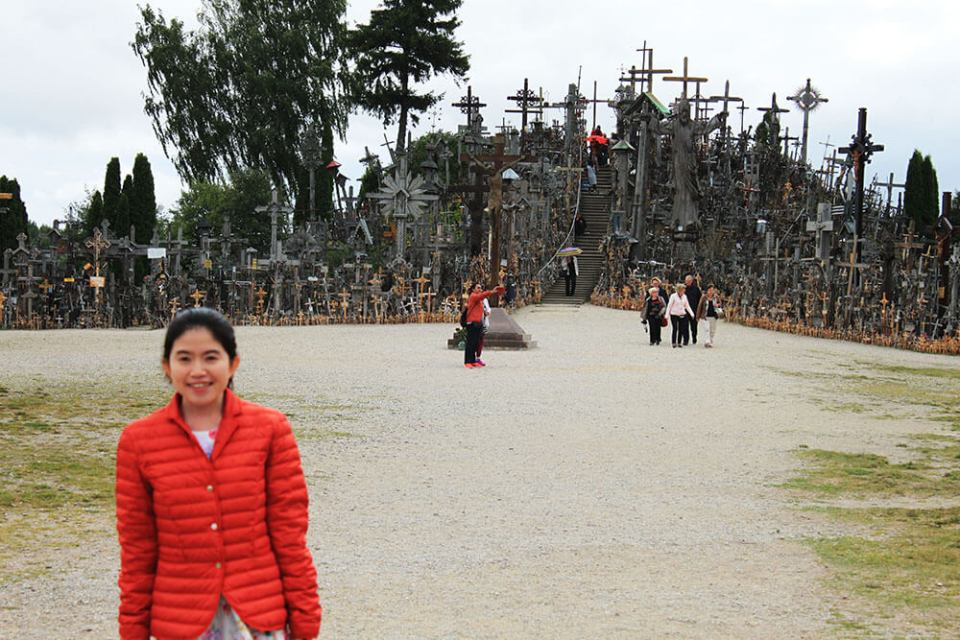 girl smilling blur with sharp background Hill of Crosses Lithuania_agirlnamedclara