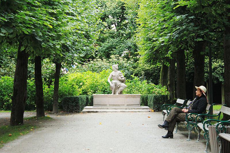 grandma sitting alone tall green trees wooden bench mirabell gardens salzburg austria_agirlnamedclara