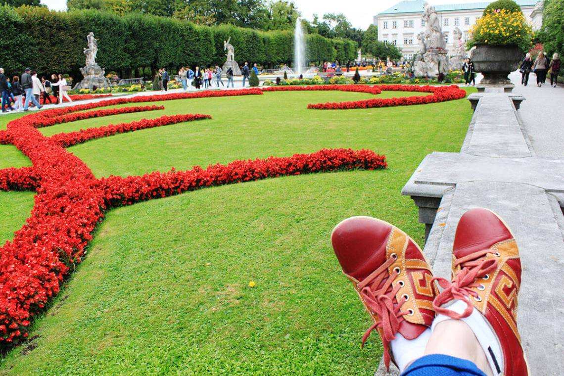 relaxing stretching legs red shoes mirabell gardens background salzburg austria earth day google bee game_agirlnamedclara