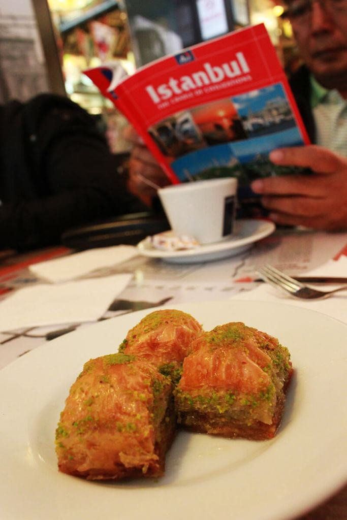 pistachio baklava turkey on a plate a man tourist reading istanbul travel guide book on dining table_agirlnamedclara