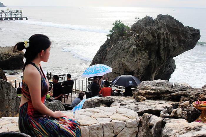 asian girl knot hair flower bareback dress feminine looking at sea rock bar bali_agirlnamedclara
