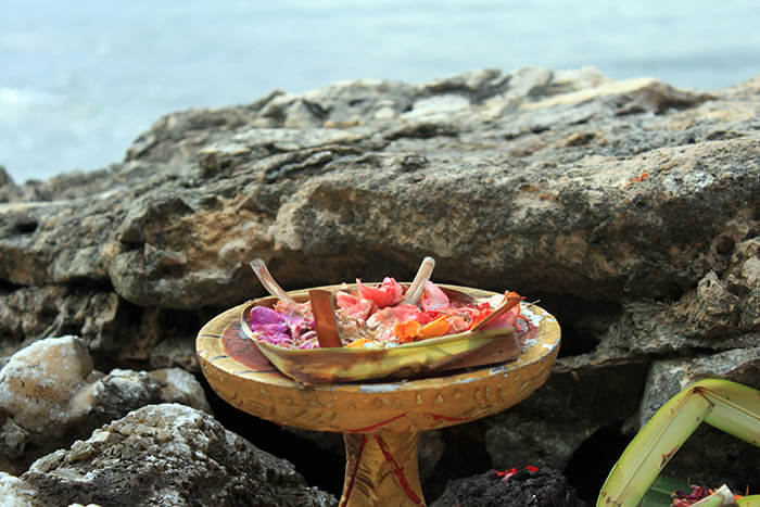 bali flower offering on cliff sea background rock bar_agirlnamedclara
