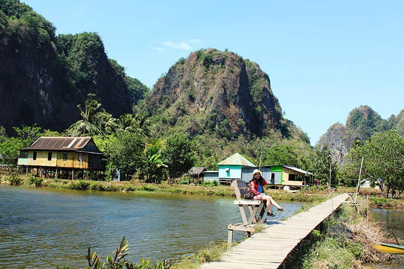 girl travel white hat sitting near dam rammang rammang hills background makassar sulawesi travel_agirlnamedclara