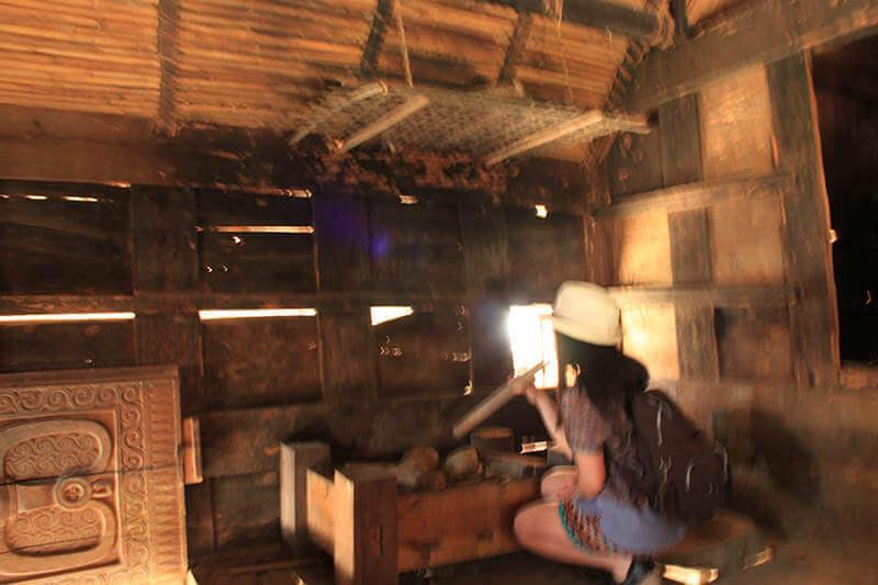 inside tongkonan interior girl tourist blow fire kete kesu toraja_agirlnamedclara