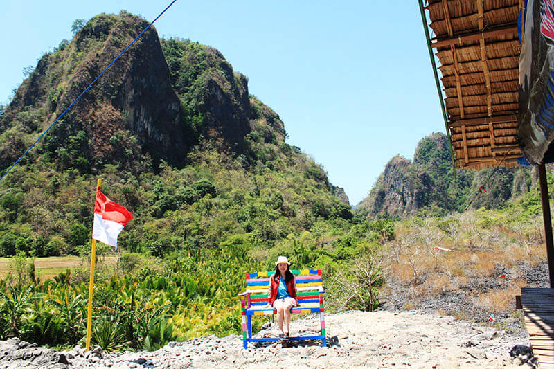 puncak rammang rammang summit indonesian flag girl sit colourful chairs smiling_agirlnamedclara