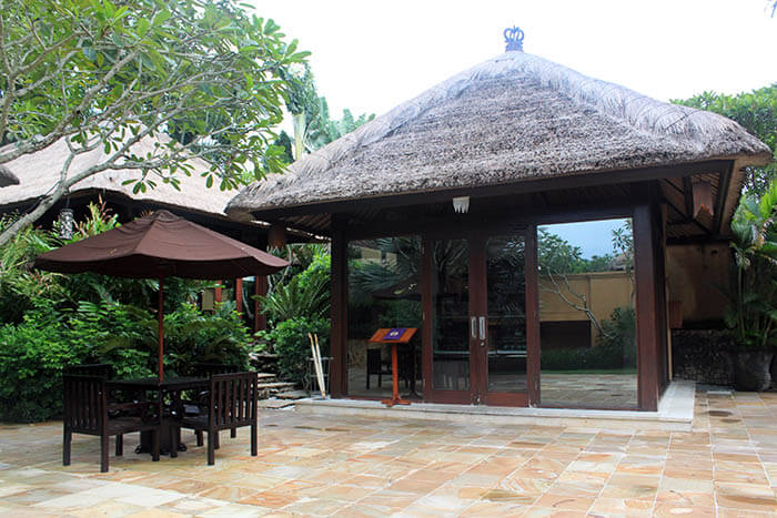 wooden hut with natural straw roof kiosk lush garden canopy table waiting area ayana resort and spa bali_agirlnamedclara