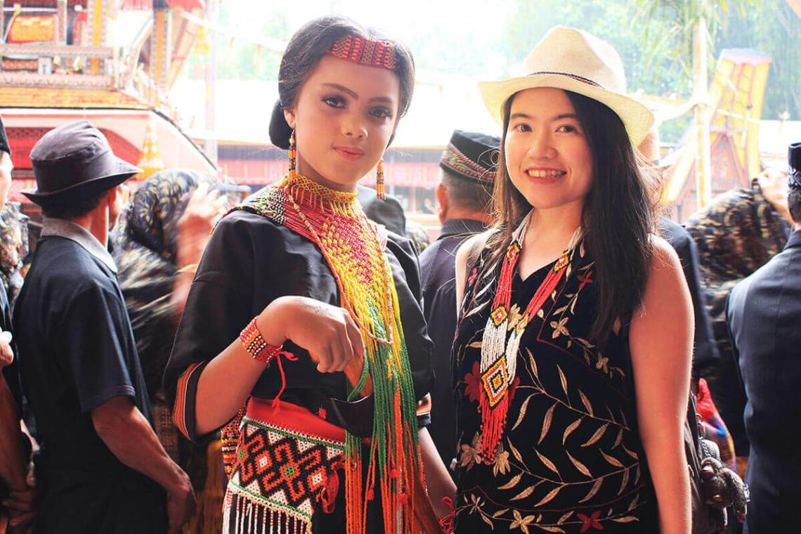 asian girl tourist traveler and toraja dancer smile rambu solo toraja_agirlnamedclara