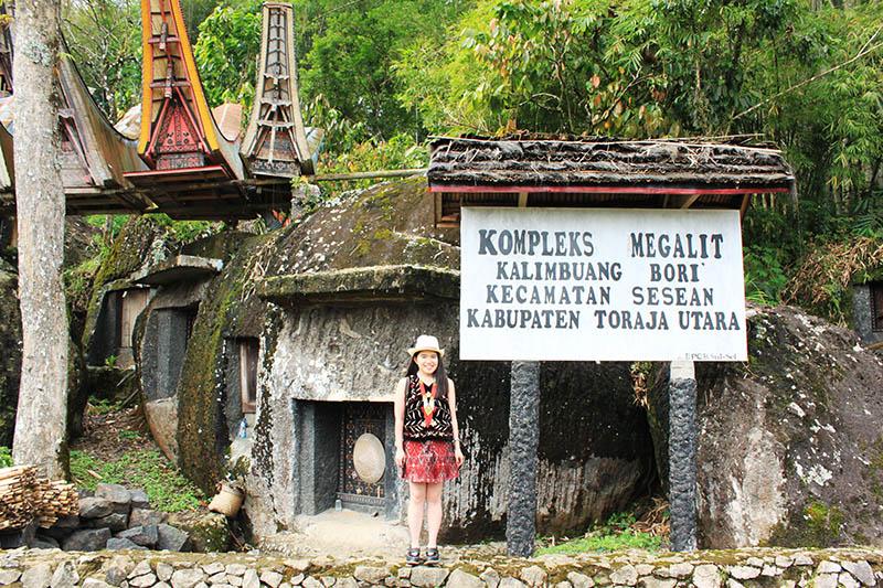 traveler wanita pose berdiri depan kompleks megalit bori toraja_agirlnamedclara