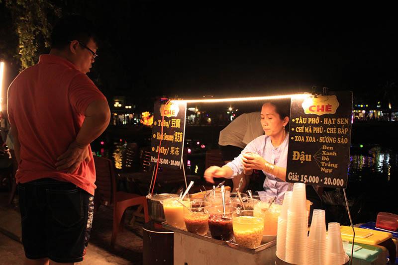 man buys sweet dessert drink hawker seller hoi an night market agirlnamedclara