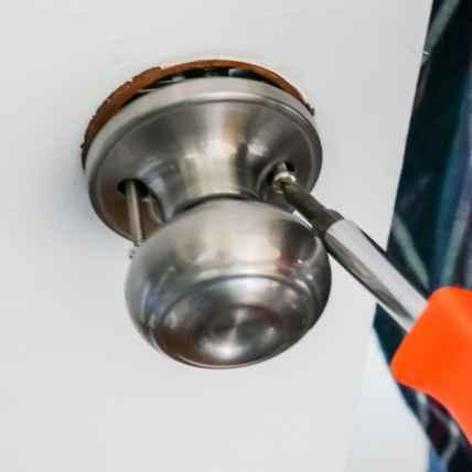 usin screwdriver to change door knob