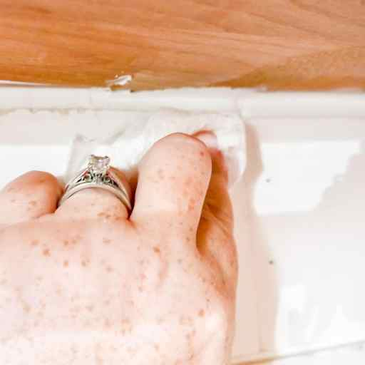 cleaning off excess caulk with a wet paper towel