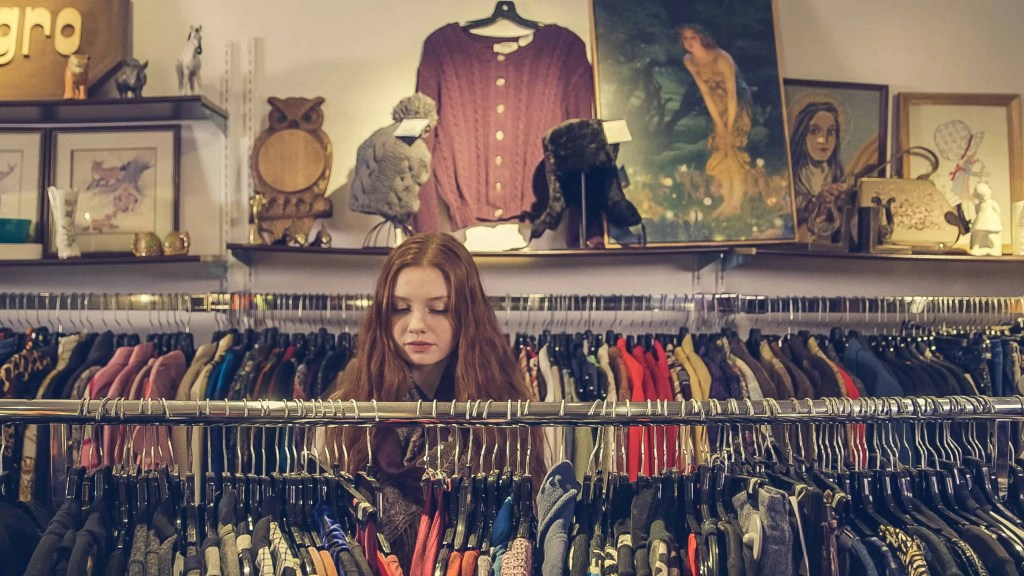 A woman shopping in a second hand, thrift, vintage clothes shop