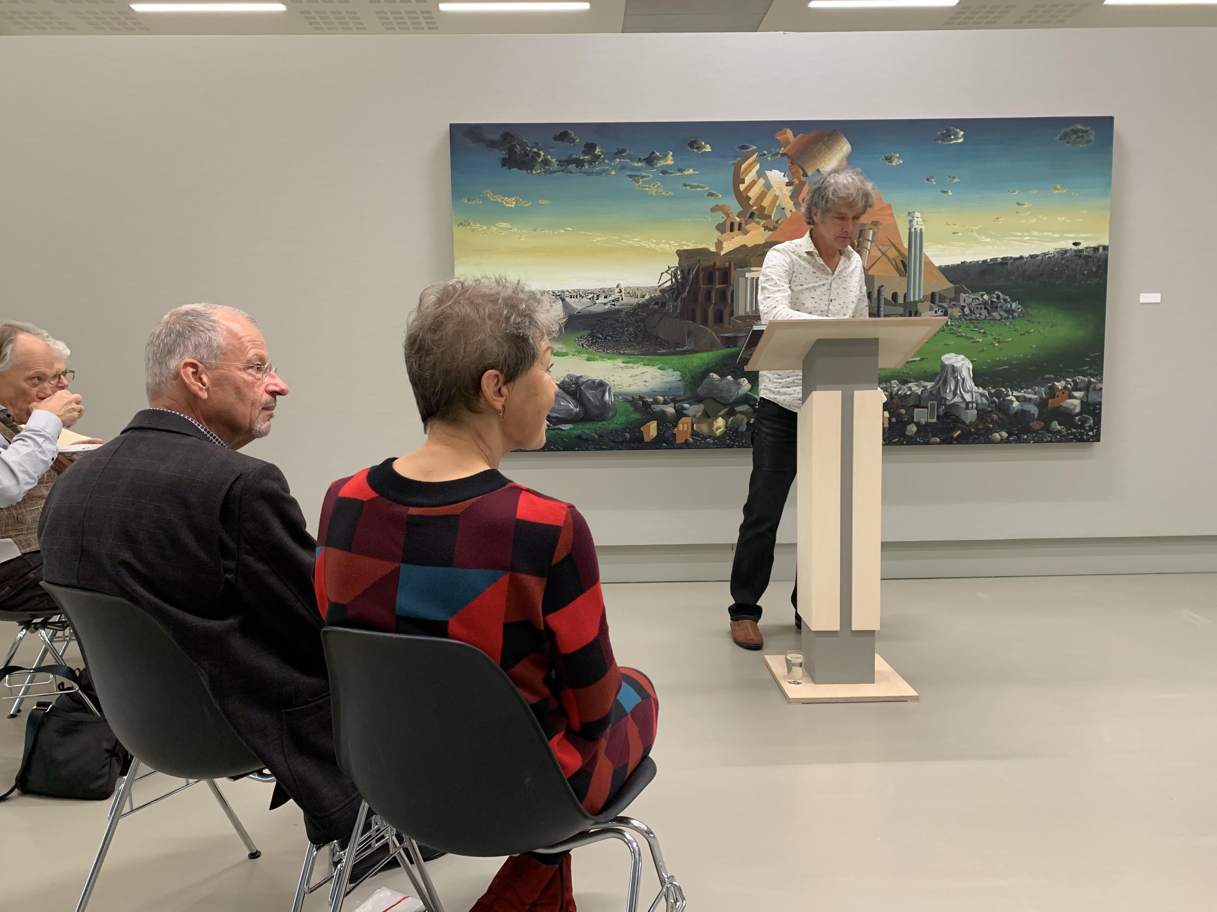 Gezicht op drie mensen die zittend luisteren naar een staande man, die met als achtergrond een schilderij een lezing geeft.