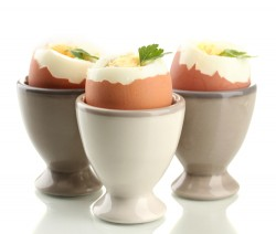 Boiled eggs in egg cup, isolated on white