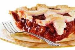 cherry pie served on a gold antique glass plate with a fork.