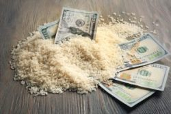 Dollar banknotes and rice grains on wooden background. Agricultural income concept