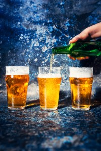 pouring beer from bottle in beer glasses