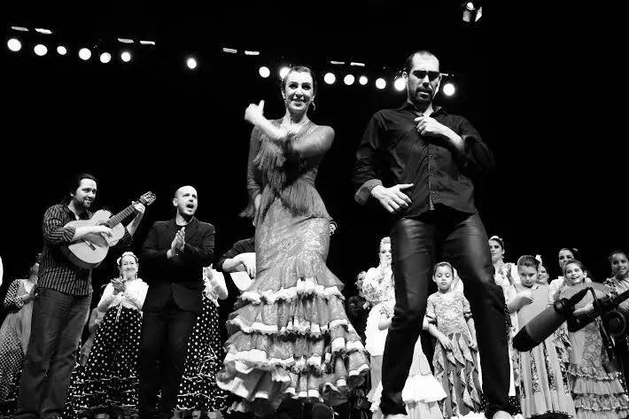 Andrea Franco e Pedro Fernández. Dançarinos à frente e músicos ao fundo, um deles canta e o outro toca violão. Diversas pessoas, inclusive crianças, batem palmas. Todos vestindo roupas típicas da região da Espanha.