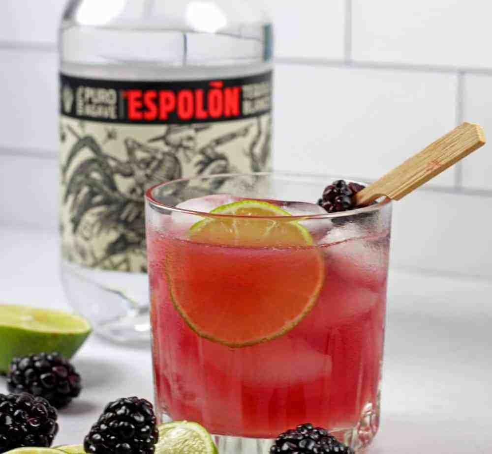 Close up of an el diablo cocktail garnished with a blackberry and lime with a bottle of tequila in the background and blackberries and limes on the side.