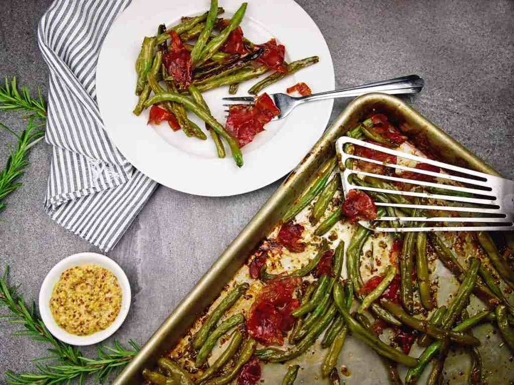overview of a plate and sheet pan of crispy green beans, prosciutto, and mustard vinaigrette