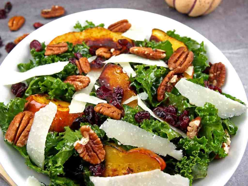 Close up of roasted acorn squash on top of massaged kale salad with pecans, shaved Parmesan, and dried cranberries in a bowl