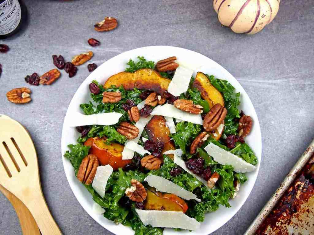 Roasted acorn squash on top of massaged kale salad with pecans, shaved Parmesan, and dried cranberries with serving utensils