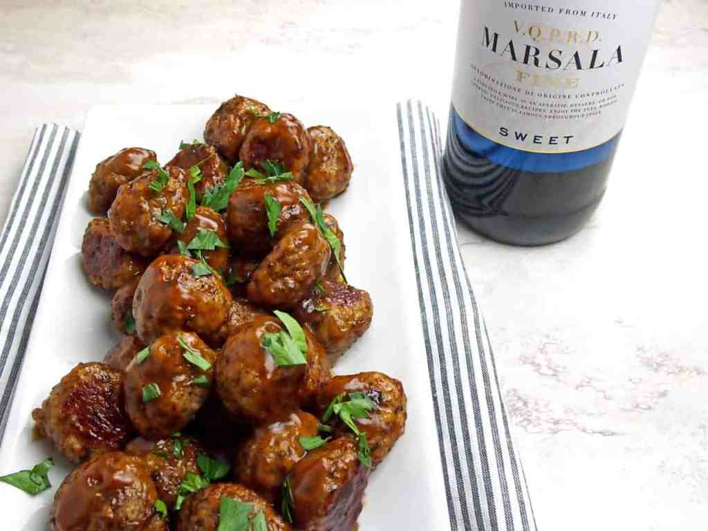 Chicken marsala meatballs with a bottle of marsala wine in the background