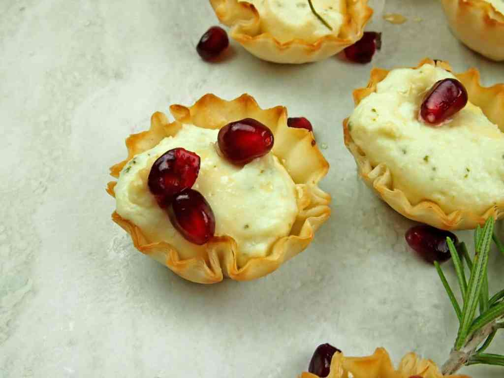 Close up of whipped feta in phyllo cups with pomegranate seeds