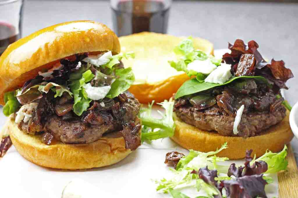 Burgers with onion, red wine, and bacon jam with spring mix and goat cheese