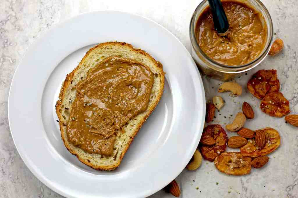 Banana nut butter on a piece of toast with a jar and nuts beside.
