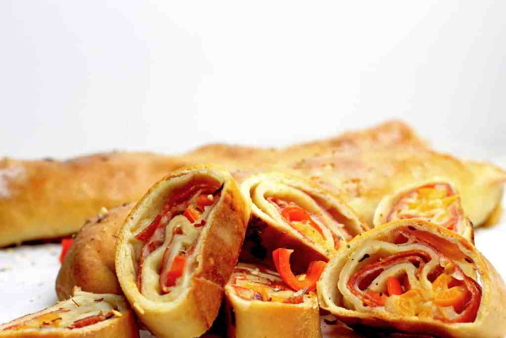 Sliced pepperoni rolls showing the pepperoni, cheese, and peppers in side on a white background.