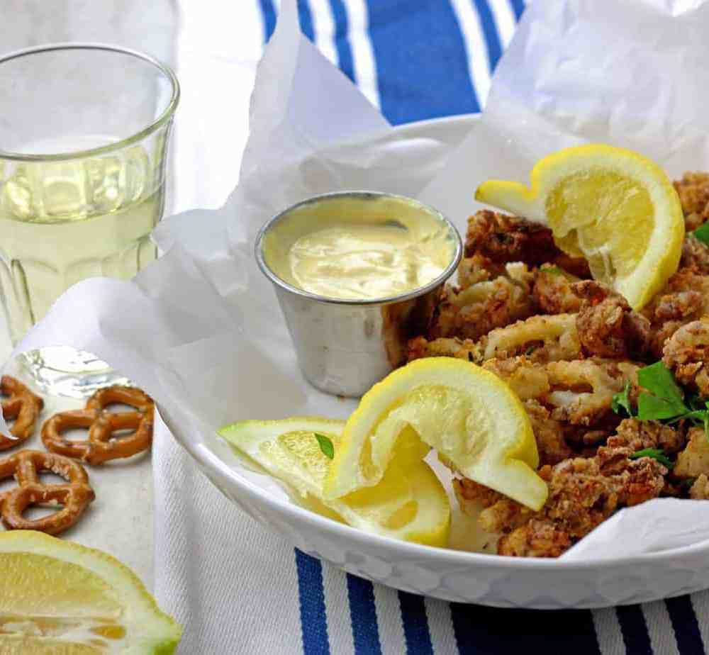 Crunchy air fryer calamari in a bowl with lemons, parsley, and mustard dipping sauce served with white wine on the side.