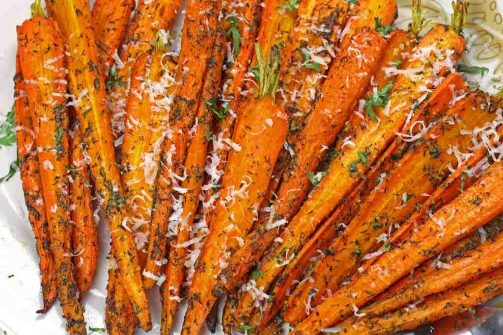 A close up of caramelized air fryer carrots on a plate topped with dill and parmesan